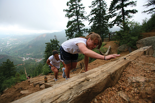 Erika Lawler strains to reach the next step on the Manitou Springs Incline ahead of teammate Jessica Koizumi.