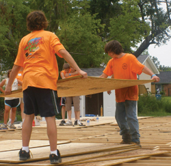 Zac Von Czoernig and Stephon Cote move a piece of plywood into place.
