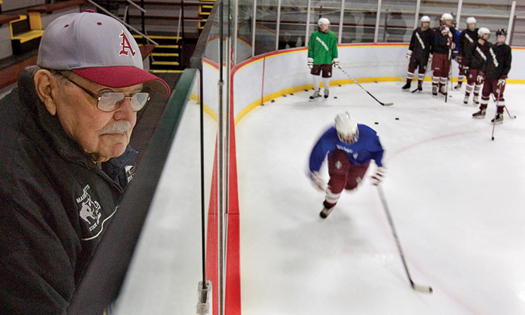 From his familiar perch in the stands, Gerry Bartholomew watches another Arlington (Mass.) practice, ensuring that kids move their feet and keep their stick on the ice.