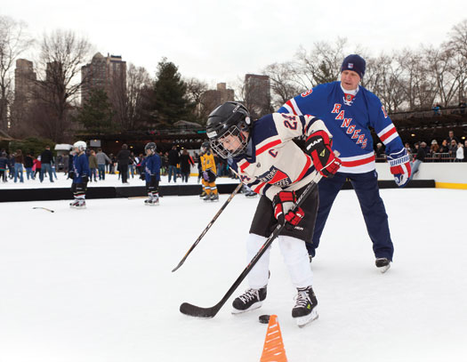 Brian Mullen plays keep-away with a young New York Rangers fan at Wollman Rink in Central Park.