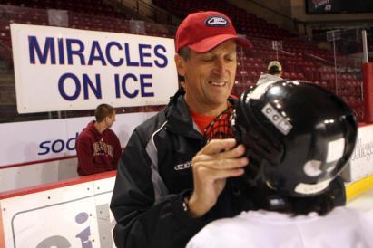 Founder of the Miracles On Ice, Gary Howard, helps strap on a helmet.