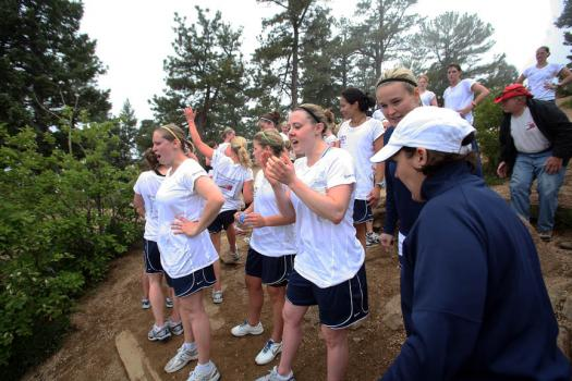 At the top of the mountain, the group cheers on their teammates who are almost to the summit
