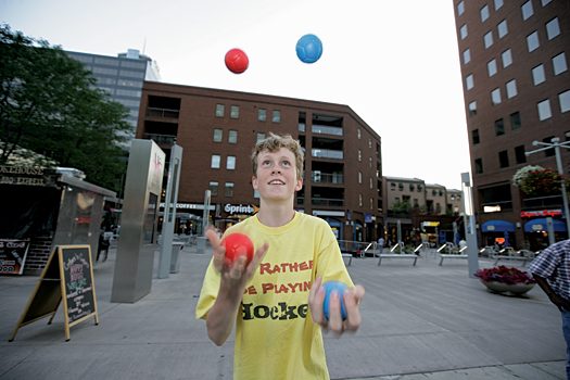 Colorado youth hockey player Will Graber juggles into the dusk of a summer night in Denver. Graber spends several nights a month on the 16th Street Mall, earning money to pay for his hockey.