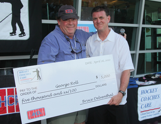 USA Hockey's Scott Paluch presents a check to George Roll on behalf of Hockey Coaches Care.