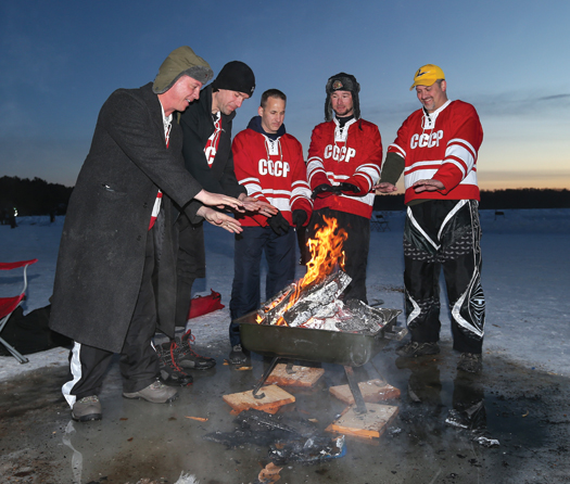 Members of the Chicago Red Army Team, below left, warm themselves at dusk following the first day of competition on Dollar Lake.