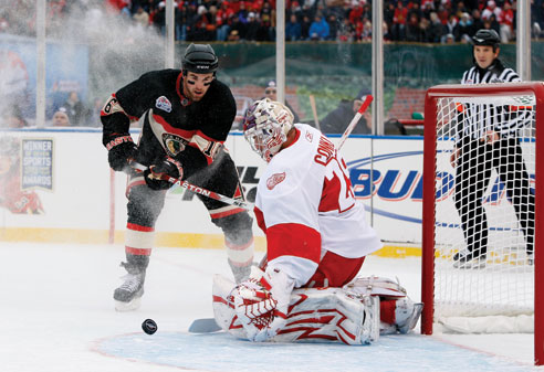 Playing in his third Winter Classic, Detroit goaltender Ty Conklin kicks aside a shot from Chicago forward Andrew Ladd.
